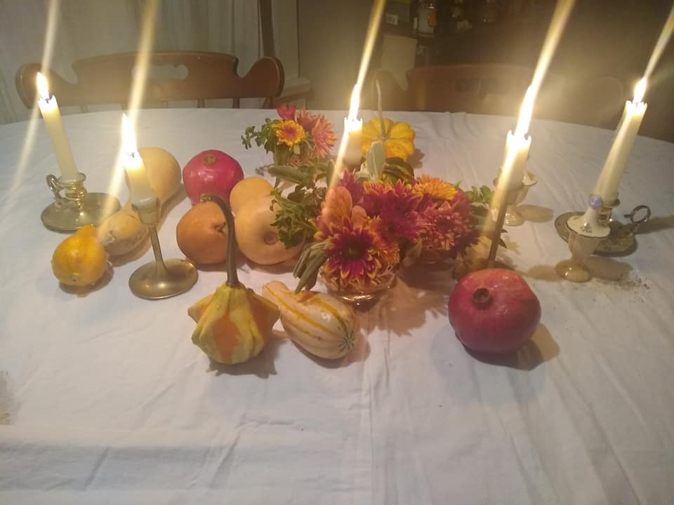 Small red, yellow, and maroon flower arrangements (with some green herbs mixed in), some decorative fall gourds, two pears, two pomegranates, tall white candles, and two butternut squash on a white table cloth.