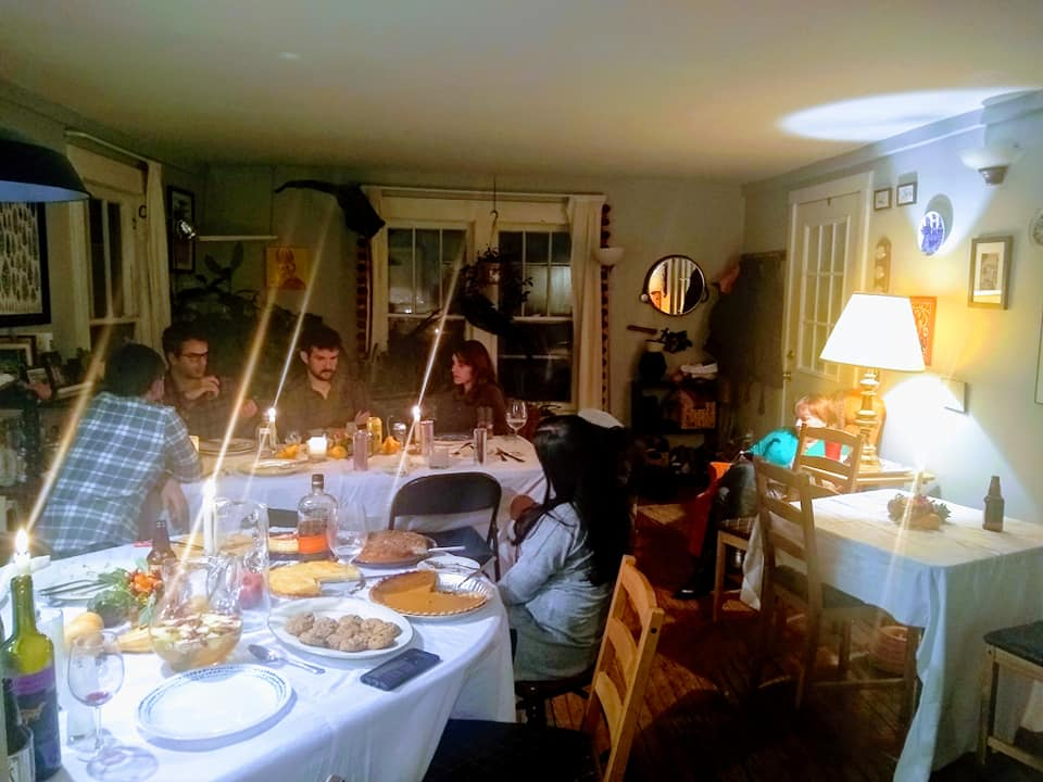 Six people talking at a white table clothed table in a small apartment, with two other smaller tables that have Thanksgiving desserts and wine bottles and candles on them.