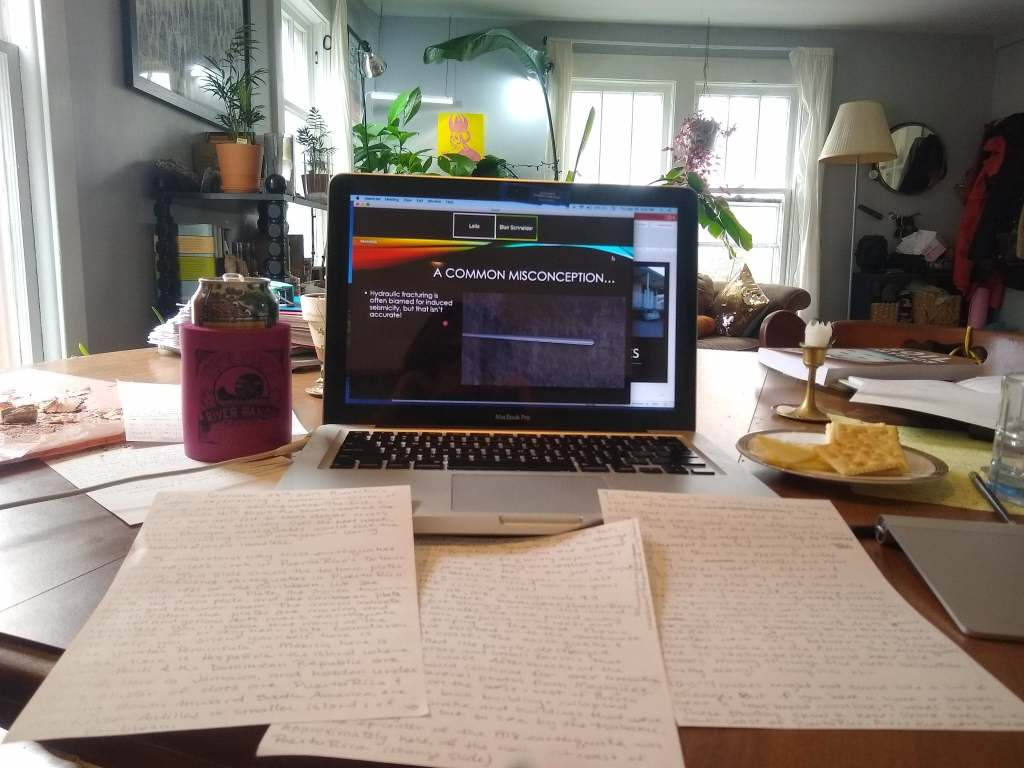 Image of home work space with laptop, notes, snacks, drinks, and plant-filled living room in the background